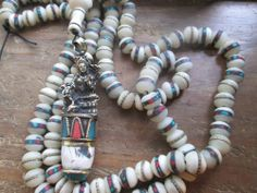 White Tara Healing Strand - A gorgeous White Tara sits atop a beautiful naga conch shell piece inlay with turquoise and copal.  The 108 beads are white carved bone (naturally shed). Wonderful strand to use in your healing practice. $65