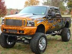 Awesome customized and lifted Ford Truck with cool paint job. The nerf bars and vent shades are two details we really like.