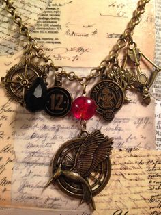 Hunger Games Catching Fire Necklace on an 18 bolo chain with Catching Fire charms.  This is part of the Charming Line by LoveEuniceDesigns, $22.00