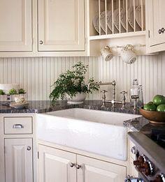 Farmhouse sink w/white cabinets and dark granite countertops
