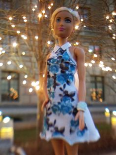 Barbie is walking through Washington DC near some lit-up trees. #artsyindc