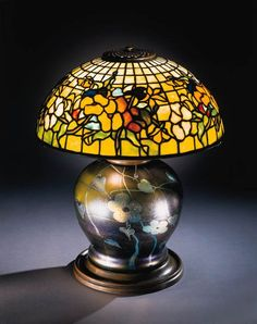 A FINE 'PANSY' LEADED GLASS, INTAGLIO-CARVED FAVRILE GLASS AND BRONZE TABLE LAMP  Tiffany Studios   the favrile glass base decorated with two small intaglio-carved bumblebees at top  19in. (48.9cm.) high, 16in. (41.2cm.) diameter of the shade, with finial  the shade tag stamped TIFFANY STUDIOS NEW YORK 1448