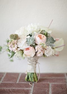 light pink peonies, cream roses, and succulents. tied with raffia.