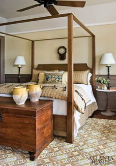 The master bedroom combines traditional elements, plaid prints, tapestry pillows and dark wainscoting with rustic touches, resulting in a sophisticated yet cozy space.