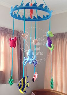 This mobile consists of a bamboo ring covered in a soft blue wave feature with a selection of sea critters hanging below it to create a bright colourful hanging for your precious little one to gaze at from their cot and adds a nice touch of colour to brighten up the nursery.  Each critter is made from quality wool/acrylic blend felt, and is hand stitched together and stuffed with polyfill, they are strung up with strong ribbon.  This makes them light weight so they gently move around in a…