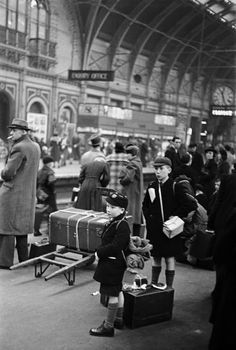 London, Paddington Station, 1940. School boys with gas masks evacuated by train as bombing raids intensify. Life in London during The Blitz of World War II.