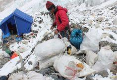 Un sherpa népalais ramasse des sacs de déchets collectés sur l'Everest, mis au jour par la fonte des glaces, le 26 mai 2010 - AFP