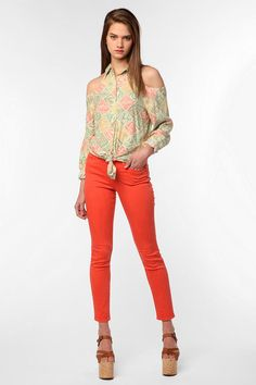 Collared off the shoulder shirt matched with orange pants to bring out the green in the shirt