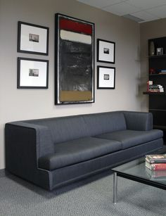 This successful Financial Advisor's office needed to exude a feeling of strength and sophistication, but be understated in its elegance. The lounge area features strong, classic modern furniture upholstered in black leather and grey wool flannel. At the far end of the space, we added a custom walnut and stainless steel wall unit composed of floating shelves, a flat-screen TV, and a bar. Drapery panels complete the space. Design by Dunlap Design Group, LLC. Photo by Chani Devers.
