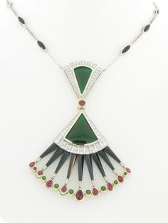 Art Deco Platinum and 18K yellow gold necklace featuring two triangular cabochon Jade pieces (4.08 ctw.), nine pear-shaped Rubies (1.65 ctw.), custom-cut Onyx, round tsavorite Garnets and round Diamonds (1.38 ctw.).