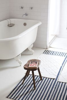 a sweet little bathroom set up -- claw foot tub, hand turned stool, striped rugs, white towels