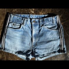 """Vintage Levi's Sporty Denim Shorts! Sooo cute! 90's Levi's jeans shorts with black and white stripe on the sides! I don't see a size but here are the measurements. Front Rise 11.5"""", Crotch to hem length 2.25"""", Waist 16.25 Levi's Shorts Jean Shorts"""
