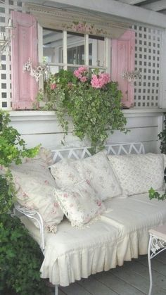 [I love this.  The pink shutters are perfect, and I like the painted pink roses above the window--or perhaps it's a mirror. I wonder why they didn't use diagonal lattice, to go with the back of the settee? The variegated ivy planted with the pink geraniums looks much nicer than a plain ivy would have.]