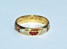 Seventeenth-century gold and enamel posy ring featuring a pair of hands holding two crowned hearts with the inscription 'Heart and Hand at your command'. ()rowanandrowan.com)