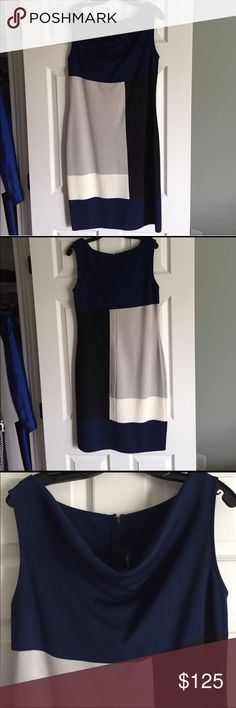 St. John Dress This St. John dress is in excellent used condition. It is the Milano knit in a color block design. The neckline is draped. The main color is navy blue. The blocked colors are black, cream and taupe. Beautiful to wear to office or dressy affair. St. John Dresses