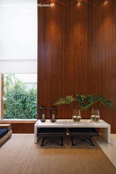 Um imenso painel em madeira acompanha o pé-direito duplo do hall de entrada, que se une ao verde do jardim lateral (Flora Decari) graças à janela em vidro com esquadria de PVC (Única PVC)