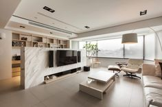 This low marble wall conceals an office space and also acts as a mount for a flatscreen.