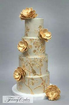 Pastel de 4 pisos con un toque de dorado y unas orquídeas en dorado