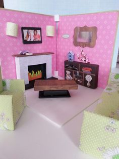 Living room with fire place using foam core board, movie size candy box, craft foam for fire place flames, and cut outs from magazines and news paper ads.