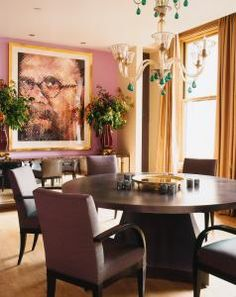 the walls are painted in an orchid tone, which creates a backdrop for the large self-portrait by artist Chuck Close. A round, steel-patina table and ebonized wood dining chairs provide a more muted touch to the decor.  But, as in all Drake's interiors, there is an element of the unexpected. Emerald beads on a glass #chandelier add a quirky touch. #interiordesign