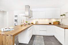 cuisine bois et blanc moderne avec des armoires blanches sans poignées et plans de travail en bois massif