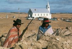 """Two activists of the American Indian movement stand guard near Sacred Heart Church during the standoff at the Pine Ridge Reservation, 1973.  Photo credit: PBS; this is a still image taken from the documentary film """"Wounded Knee."""" — in Wounded Knee, South Dakota."""