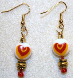 Handcrafted by Teal Palmetto, LLC.  These earrings are a modern take on Valentine jewelry.  The double-heart design is produced within the smooth, white lampwork glass beads.  Gold metal, as well as red and gold, glass accent beads add sparkle.  This pair has gold fish hook ear wires.  Price: $15.