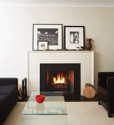 A simple MDF mantel offers an affordable update.    An old Art Deco-style fireplace was replaced with a crisp, white-painted wood mantel and minimalist surround. The new fireplace boasts clean lines that complement the contemporary look of the rest of the house. A glass waterfall coffee table provides a place to rest glasses without blocking the fireplace view.