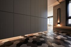 Unique architectural details make this home even more fascinating. Here, geometric tile in the entryway seeps under the suspended partition wall and into the kitchen on the opposite side.