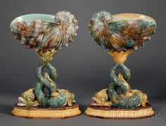 Two Wedgwood Majolica Shell Compotes, England, c. 1870, each polychrome decorated with a nautilus shell set atop the entwined tails of two dolphins, impressed marks, ht. 16 1/2 in.  |  SOLD $8,295