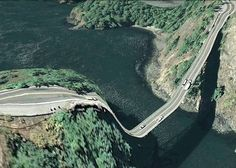 Postcards from Google Earth/ manmade structures appear to be melting over the landscapes; the program shows warped linear figures such as roads and bridges in its effort to convert 3D space to a 2D screen.