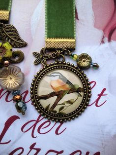 This moss green velvet ribbon is decorated with a cabochon, charms ( flower, tree, leaf, bird ) and some Czech glass flowers and beads. Reflections on the cabochon are only on the photos and not in reality. The ribbon is 11,81 inch long and 0,63 inch wide.