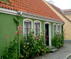 love the hollyhocks outside this danish cottage