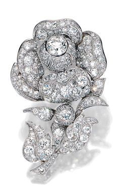 DIAMOND BROOCH. The stylised peony flower pavé-set throughout with millegrain-set circular- and single-cut diamonds.
