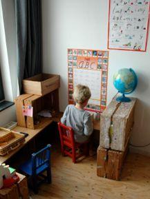 De woordenwinkel (Of: De lees en schrijfhoek) Van een paar oude kisten en planken hebben we een hoekje ingericht waar van alles te doen is met letters. De kinderen maken hier zelf woordjes die ze naschrijven van de posters of uit boekjes, voor hen is het dus de woordenwinkel.  Wij gebruikten: Kisten en planken, letterposter, woordenposter, eenvoudige leesboekjes, papier en pennen, letterkaarten, voelletters, oud toetsenbord, een kassa en nog wat losse rotzooi.