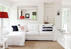 Divaanisohvalta on näkymät terassille ja metsään. Kunnostamani jakkara on mökin edellisten omistajien jäämistöä. Espanjalainen valaisin on alennusmyyntilöytö S.A.L.I.:sta. Sohva, matto ja hopeakehyksinen peili ovat Ikeasta. Gantin tummansininen tyyny ja valkoinen tyyny ovat Stockmannilta. Valokuvakehys seinällä ja raidallinen tyyny ovat Rivièra Maisonilta. Tarjotinpöytä Roltrade. Nautical Interior, Nautical Home, Nautical Style, Coastal Style, Lakeside Living, Coastal Living, Small Space Living, Small Spaces, Upholstered Furniture