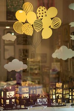 Interesting papercut window display prop.  I also like the cardstock balloon arrangement which could be adapted for a variety of display scenarios and used over a craft fair table