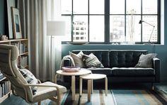 Vardagsrum med svart 2-sits lädersoffa och fåtölj med beige plymå och björkstomme. Här med två satsbord i björkfaner.
