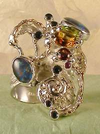 pinned from http://www.designerartjewellery.com/opaljewelry.htm  Ring with opal triplet, faceted sapphires, faceted ruby, faceted garnet, peridot, and citrine