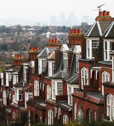 The Edwardian houses of steep Muswell Hill, a suburban street in the north part of greater London, England. The background view is Canary Wharf; one of London's major business districts