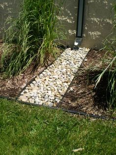 draining the rain water - build up on east side of house with drain and rocks out to other rocks