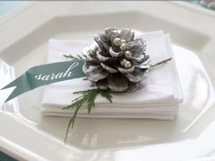 Sparkling Pinecones Dress up a simple place setting with a pinecone and name tag cut from scrapbook paper and attached to a whitewashed pinecone studded with silver dragees. Photo by Matthew Mead.