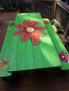 Finished whimsical flower painted green  picnic table. By Denise Walker
