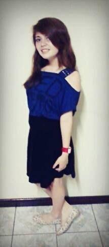 Saia de cintura alta preta  , blusa azul e sapatilha de flor com fundo branco.