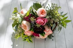 Wedding bouquet of peach juliet garden roses, pink romantic antike garden roses, burgundy dahlias, blue viburnum berries and textured foliages; flowers by www.redpoppyfloral.com