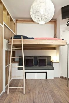 Murphy loft bed. Instead of being positioned lower on the wall like a typical Murphy bed, this version folds up high, allowing the lower level to remain usable, even when the bed is down. A ladder (stowed away in a closet between uses) provides access to the bed, while high built-in storage becomes a nightstand.