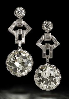 An impressive pair of diamond pendent earrings, circa 1960 Each articulated drop claw-set with an old brilliant-cut diamond, weighing 10.55 and 10.42 carats respectively, suspended from a smaller old brilliant-cut diamond surmount via an openwork baguette-cut diamond geometric connecting link, length 4.5cm.