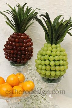 Grapes to form pineapple formed table centerpieces in candlestick vase