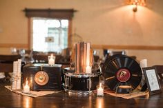 "Music-themed wedding table centerpiece - vintage style! Vintage RCA bakelite Radio, old, 78's ceramic records, vintage hymnal books, and rolled vintage sheet music in vintage ""Ball"" brand mason jars.   Union Hill Inn Wedding - March 2016  http://www.americanvintagerentals.com/decor#page"