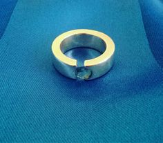 A beautiful heavy silver ring. Set with a blue topaz in an interesting tension setting. Very thick solid sterling silver. Ring size M, US size 6 and a half. A quarter of an inch wide.